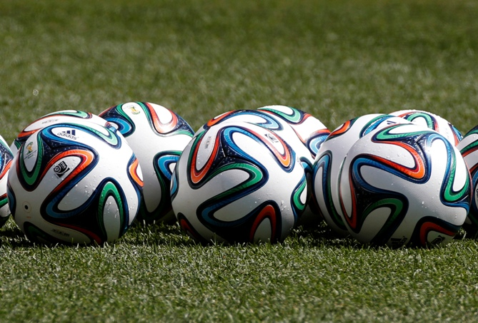Official 2014 FIFA World Cup Brazil footballs sit on the pitch.