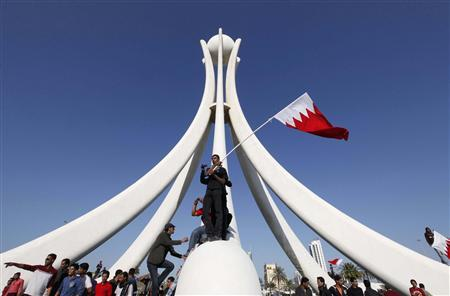 Protesters stand at the base of the Pearl Roundabout in the Bahraini capital of Manama, February 15, 2011.