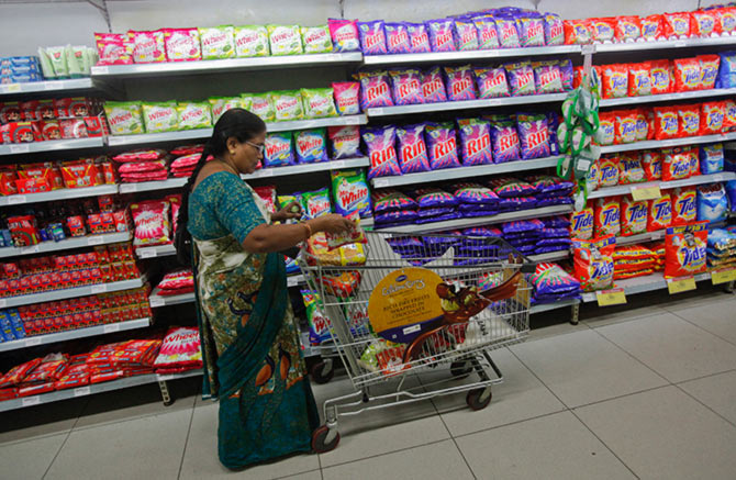 A woman fills her trolley with retail products as she shops at a Hypercity department store, one of Mumbai's largest.