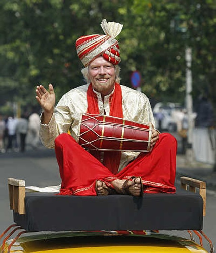 Virgin Group founder Richard Branson plays a dhol while sitting atop a taxi during a promotional event in Mumbai.