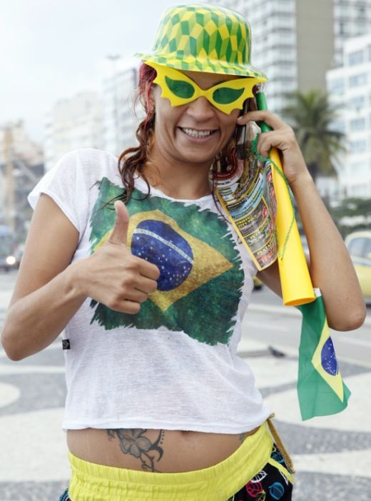 A Brazilian fan gives a thumbs up on Copacabana Beach as the 2014 FIFA World Cup nears.