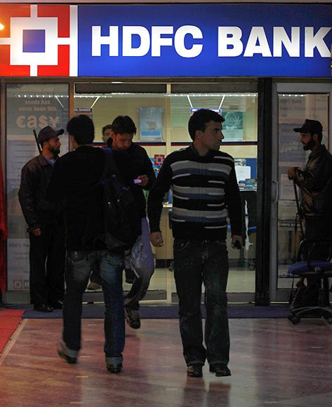 People walk in and out of a HDFC bank branch in Srinagar.