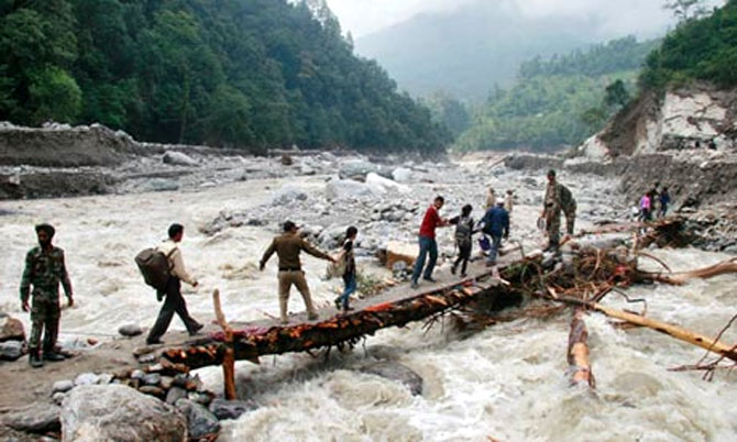 File photo of rescuers helping stranded people cross a flooded river in Uttarakhand.