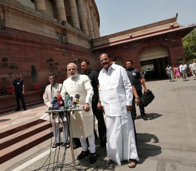 India's Prime Minister Narendra Modi (C) speaks with the media as he arrives to attend his first Parliament session in New Delhi June 4, 2014.