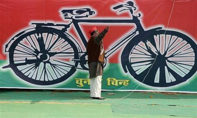 A Samajwadi Party worker gestures in front of a banner with the party's electoral symbol.