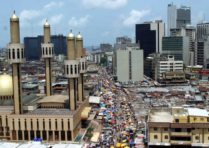 People and traffic move along a busy street in Lagos.