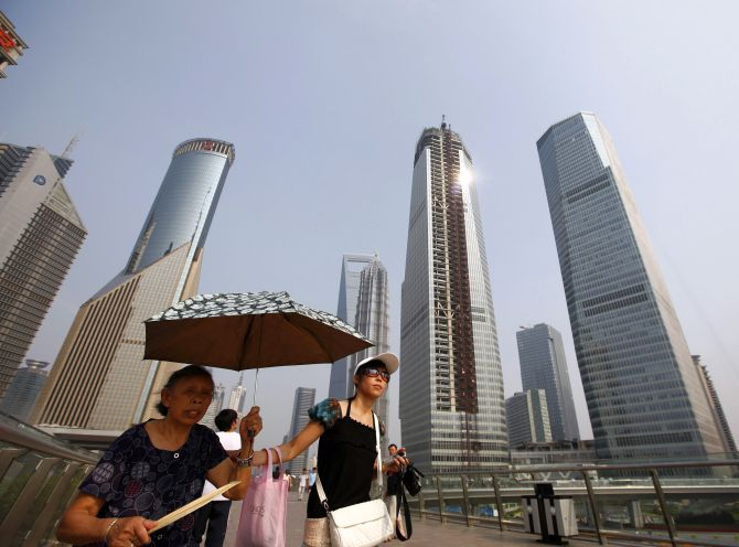 Visitors walk through the Lujiazui Financial Area in Shanghai.