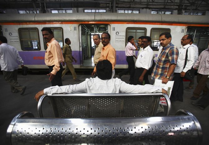 Commuters pass by as a man sits and waits for a train at Church Gate railway station in Mumbai.