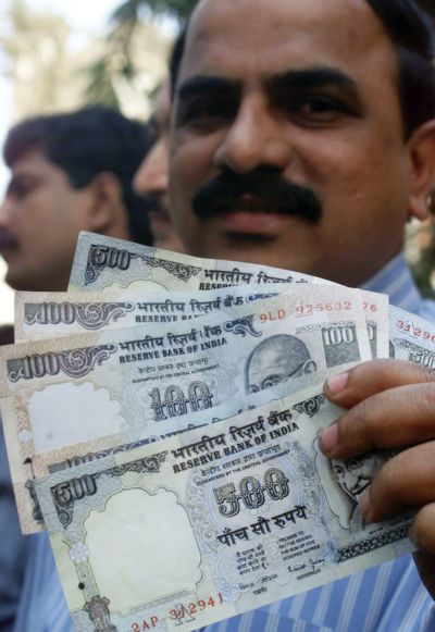 A policeman displays counterfeit currency seized in a raid in Mumbai.
