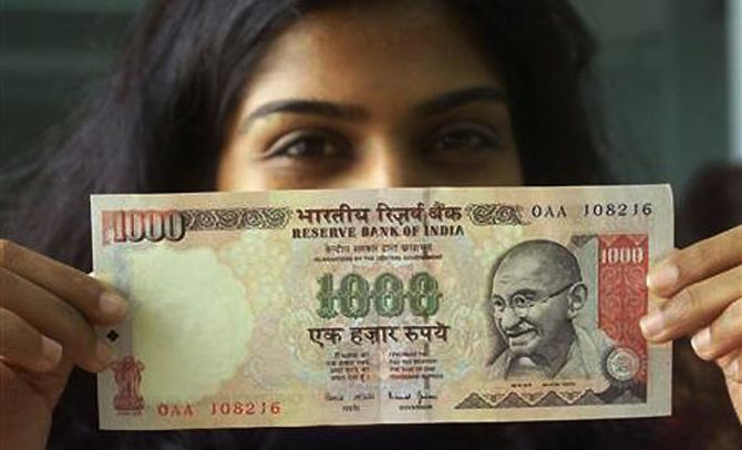 A girl displays a 1000 rupee note.