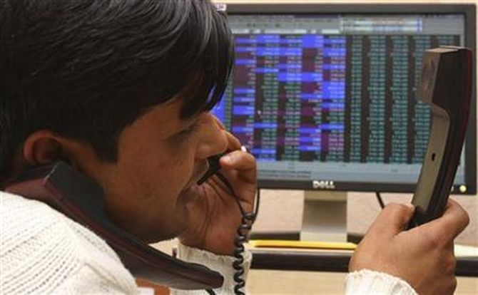 A terminal operator speaks on telephones at a local stock market