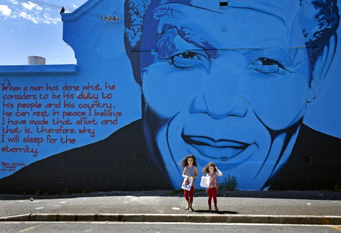 India Harris, age eight, and her sister Kitty, five, stand in front of a Nelson Mandela wall mural.