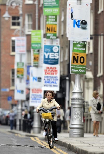A woman cycles past posters in central Dublin.