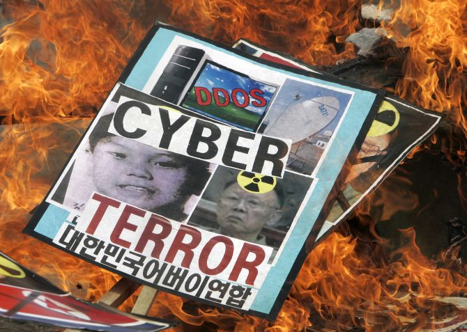 Conservative protesters burn portraits of North Korea's Kim Jong-il (R) and his son Kim Jong-un during an anti-North Korea rally denouncing the North's cyber attacks.