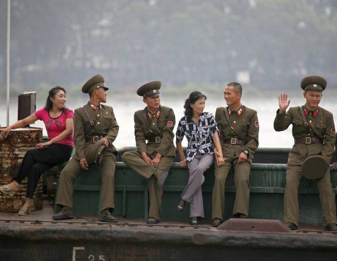 A North Korean soldier waves to a Chinese tourist boat on the Yalu River near the North Korean town of Sinuiju.