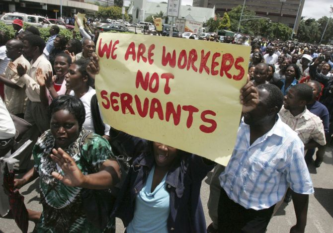 Zimbabwe's civil servants carry placards as they march during a protest.