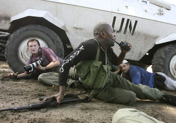 Reuters Congo correspondent David Lewis (L) takes cover behind a U.N. armoured car during machine gun and mortar fire in Kinshasa.