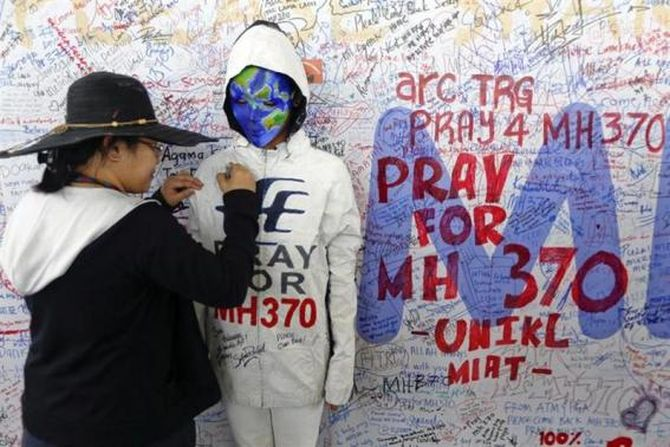 A woman adds her message on the clothes of a model during an art performance in support of the passengers of the missing Malaysia Airlines MH370 at the departure hall of Kuala Lumpur International Airport March 17, 2014.