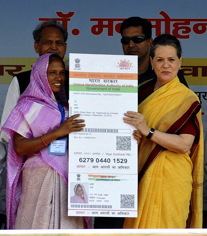 Chief of Congress party Sonia Gandhi (R) presents the 210 millionth biometric card to Vali , a villager residing in Rajasthan.