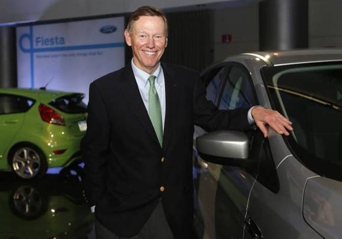 Ford Motor Co. CEO Alan Mulally poses next to a Ford vehicle during a gathering with members of the media at the Ford Conference Center in Dearborn, Michigan.