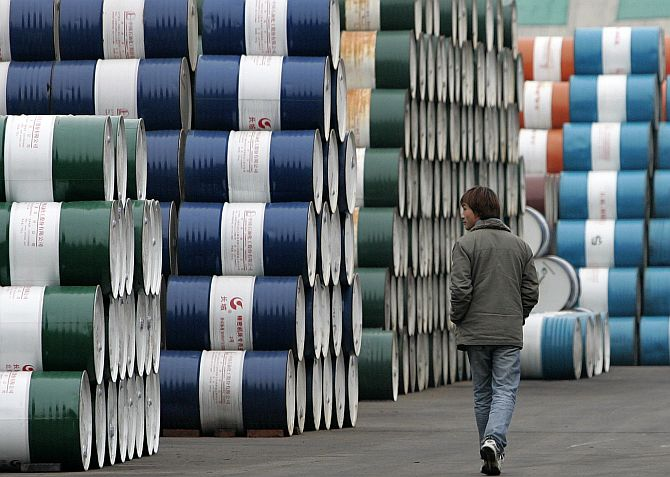 A man walks past a storage area for oil barrels in Shanghai.