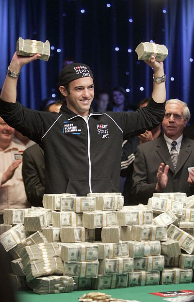 Joe Cada, a poker professional, celebrates with bundles of cash after winning $8.5 million in prize money.