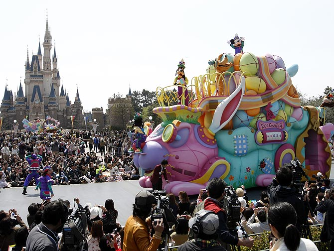 Disney character Mickey Mouse (top) performs atop a float during a parade at Tokyo Disneyland.