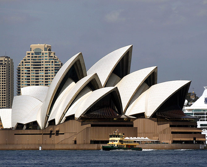A cruise liner is seen behind the Sydney Opera House along the central business district in Sydney.