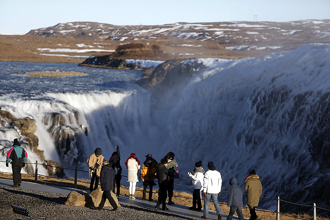 People walk near Gullfoss waterfall in southwestern Iceland.
