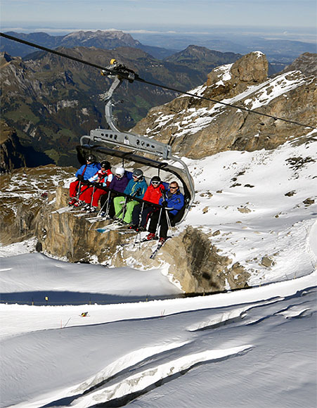 Skiers sit in a chairlift at the Mount Titlis skiing area (3,238 m/10,623 ft) near the Swiss mountain resort of Engelberg.