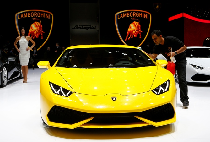 An employee cleans Lamborghini Huracan during the media day ahead of the 84th Geneva Motor Show at the Palexpo Arena in Geneva March 4, 2014.