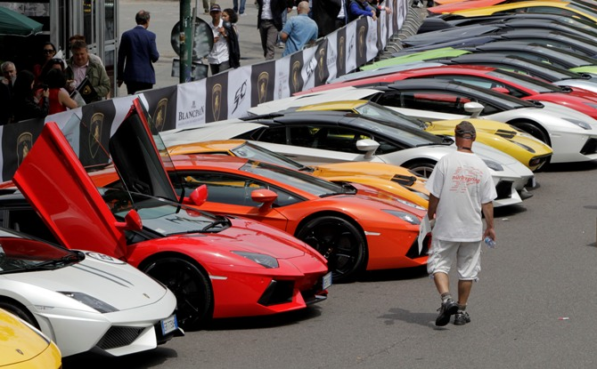 A man walks past Lamborghini sports cars parked at a car paddock during an event to mark the 50th anniversary of the carmaker in downtown Milan.