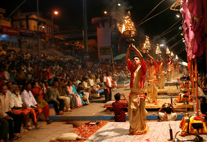 Hindu priests hold fire lamps as they perform evening prayers on the banks of river Ganges in Varanasi.