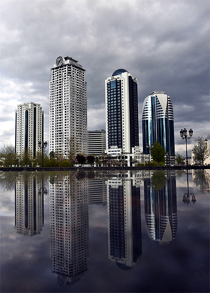 The skyscrapers are against the city skyline.