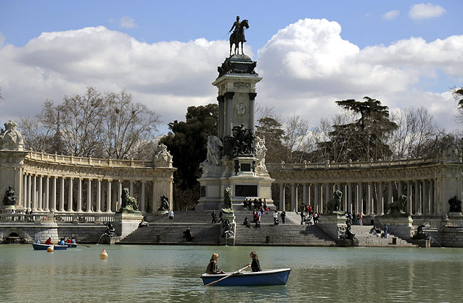 People enjoy the warm weather as they sit in boats during a sunny spring day at Madrid's Retiro park.