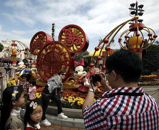 Mainland Chinese visitors pose in front of a Chinese New Year installation inside Hong Kong Disneyland.