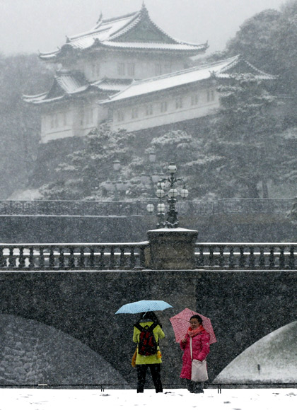Visitors take photos at the Imperial Palace as snow falls in Tokyo.