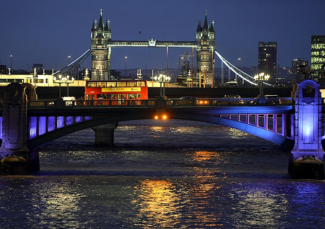 A London bus crosses the River Thames on London Bridge during the evening rush hour with Tower Bridge seen behind in London.