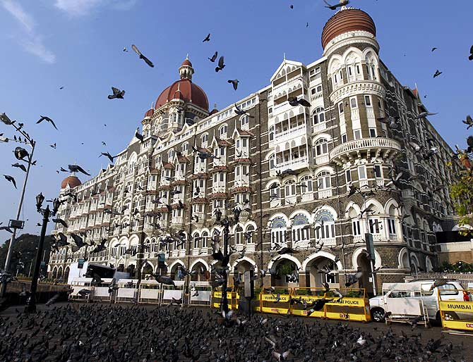 Pigeons fly in front of the Taj Mahal hotel in Mumbai.