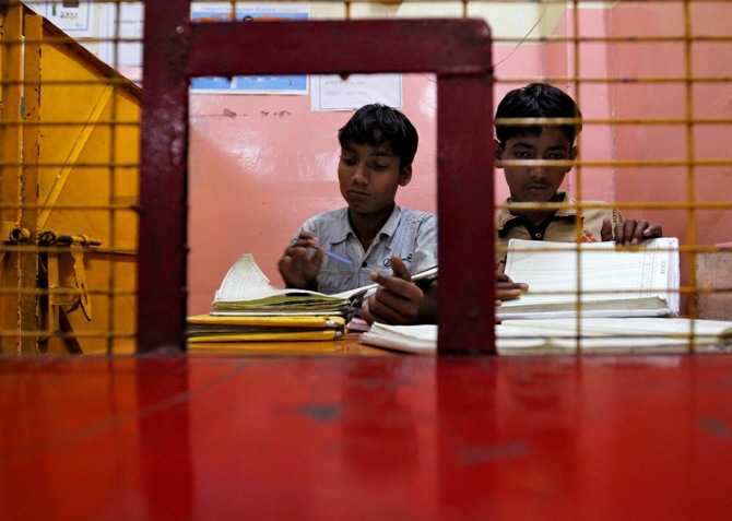 Street children check account books for their customers, also street children, at a bank supported by a local NGO in the old quarter of Delhi.