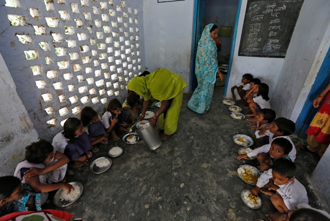 A cook serves the free mid-day meal, distributed by a government-run primary school, to children at Brahimpur village in Chapra district of Bihar.