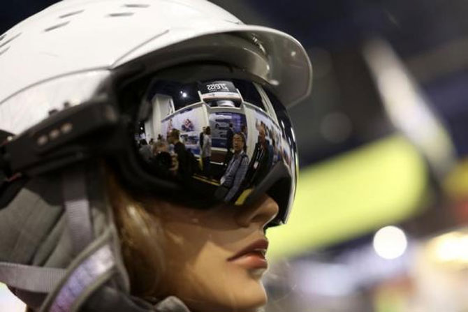 People are reflected in the lens of a pair of Liquid Image Apex HD camera goggles, capable of video and still photography.