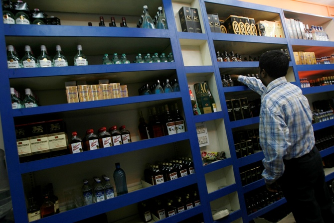 A man checks out an alcohol bottle inside a wine shop.