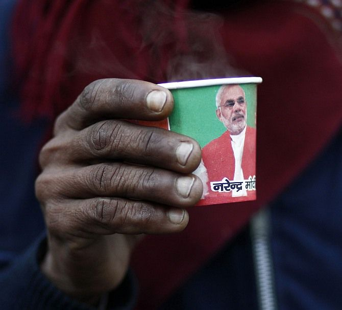 A man holds a paper cup carrying a portrait of Gujarat's chief minister and Hindu nationalist Narendra Modi, the prime ministerial candidate for India's main opposition Bharatiya Janata Party.