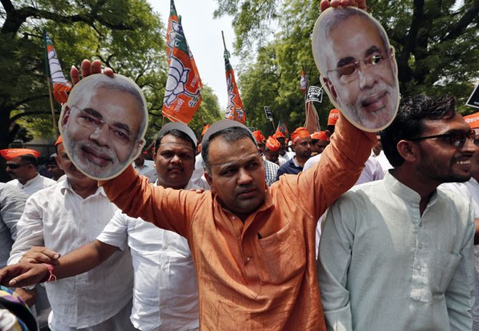 A supporter of India's main opposition BJP holds cut-outs of their prime ministerial candidate Narendra Modi.