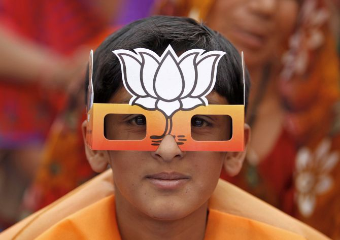 A boy wearing paper goggles featuring a lotus attends an election campaign rally addressed by Hindu nationalist Narendra Modi.