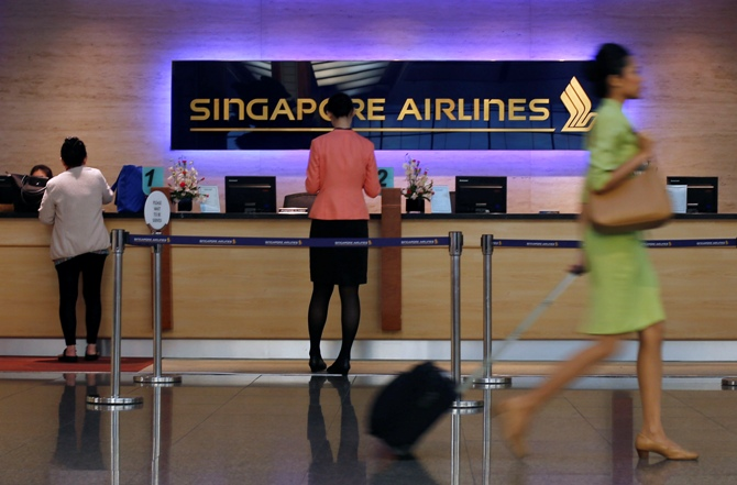 People walk past a Singapore Airlines ticketing counter at Changi Airport in Singapore.