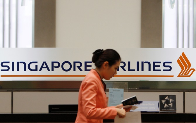 A staff member walks by a Singapore Airlines (SIA) logo at a ticketing counter.