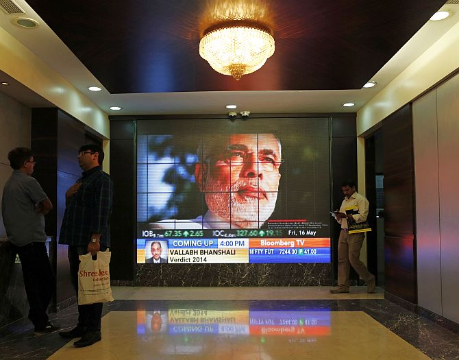 People look at a screen displaying the election results coverage on a screen inside the Bombay Stock Exchange (BSE) building in Mumbai.