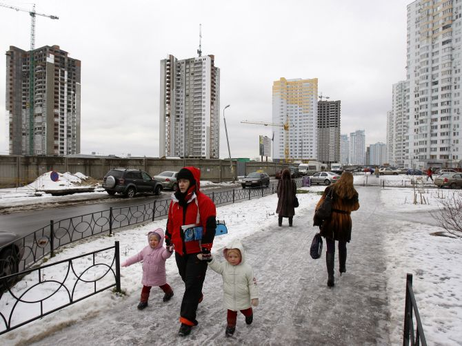 People walk in a residential district dotted with unfinished apartment buildings in Kiev D.